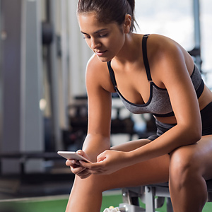 Frau mit Handy beim Training